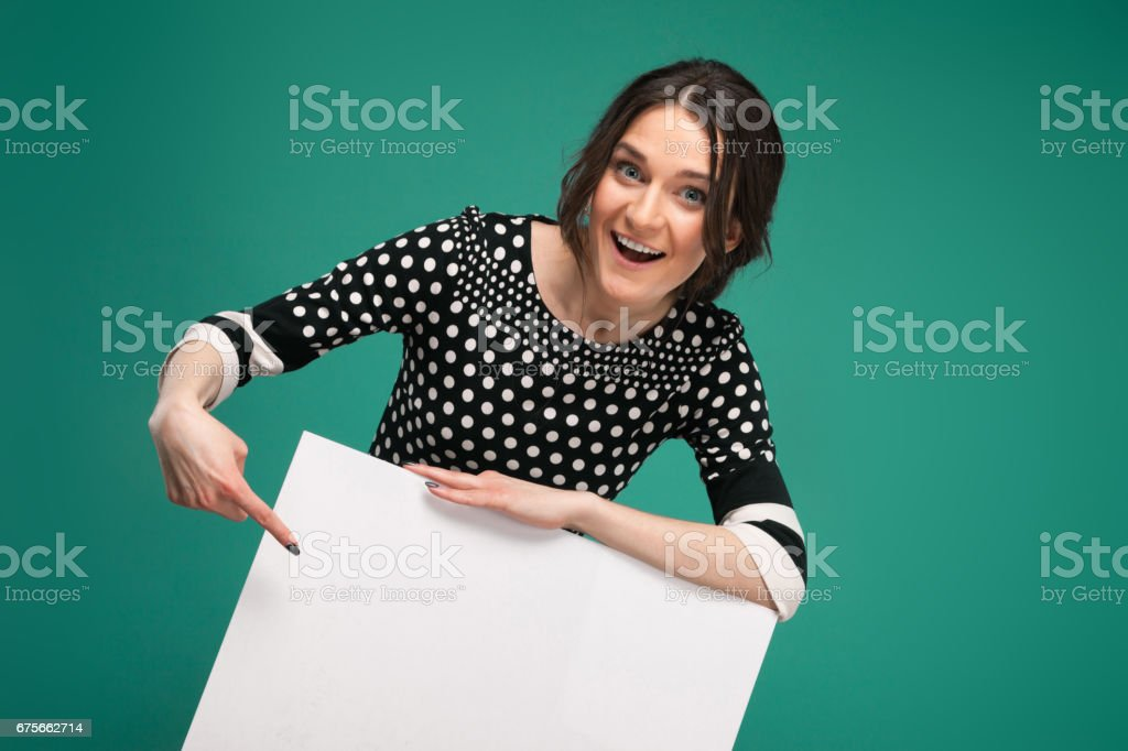 Image of beautiful woman in speckled clothes standing with paper in hands royalty-free stock photo