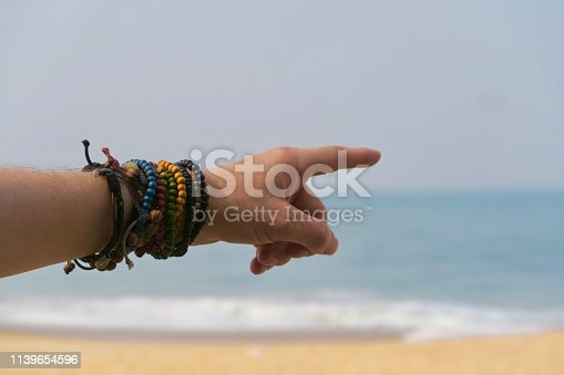 Photo showing beautiful wrist with colourful beaded bracelets against the blue Arabian Sea and Golden Sand in the kerela state of India. These colourful beaded friendship bracelets are dramatic and funky.