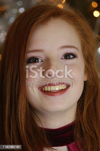 Stock photo of beautiful young woman with red hair with yellow teeth needing dentist teeth whitening whitened / pretty teenage girl 14 / 15 / 16 years old with ginger hair at New Year's Eve party, wearing red velvet party dress, Christmas tree fairy lights