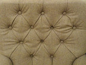 Image of beige, padded, button-studded, fabric bed headboard, background