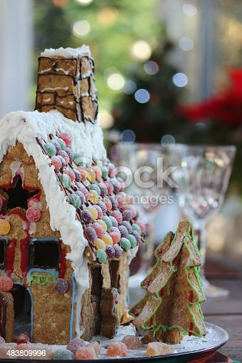 Photo showing a gingerbread house decorated with sweets and displayed on the Christmas table, which is laid ready for dinner, with wine glasses.  Roof tiles made from sweets have been used as decorations on the roof.