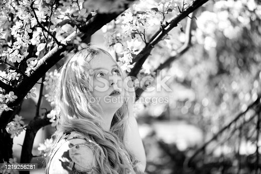 Horizontal outdoor garden shot of young blonde woman looking up into branches of spring flowering crab apple tree.