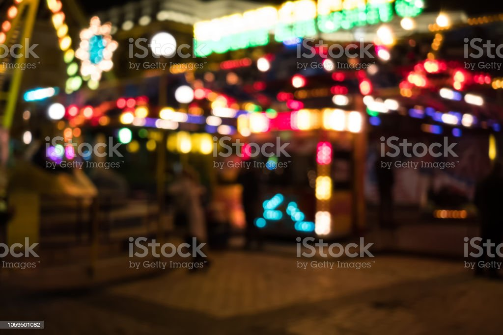 Image of blur street with festive lights and carousel in night time....