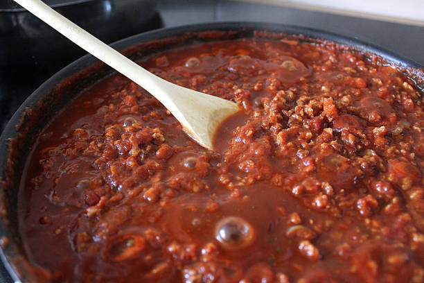Image of Bolognese sauce cooking in frying pan, wooden spoon stock photo