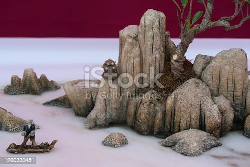 Stock photo showing a Japanese inspired miniature garden with bonsai tree planted in stones representing a mountainous scene.