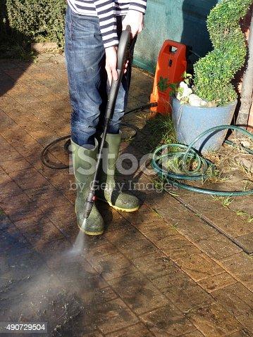 istock Image of boy washing block-paved driveway with powerwasher hose pipe 490729504