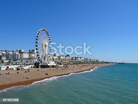 Photo showing the big wheel attraction at Brighton beach, next to the pier.  The beach is pictured in the morning, when the sun is shining and tourists are sunbathing on the sandy shingle / pebbles.