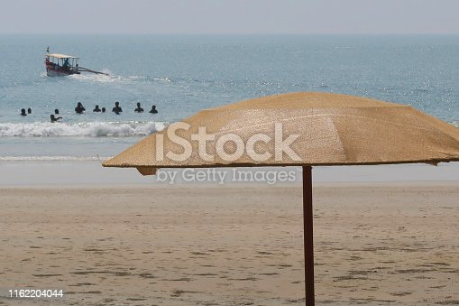 Stock photo showing parasols on Palolem Beach, Goa, India with holidaymakers swimming in the sea viewable in the distance.