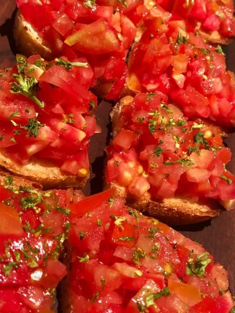 Image of bruschetta at Italian restaurant with herbs, tomato on bread served on wooden platter, healthy snack on dining table, starter appetiser dinner stock photo