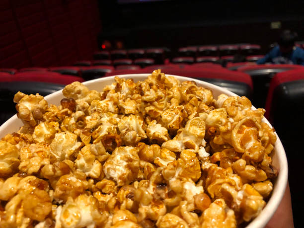 Image of bucket of popcorn in cinema / movie theatre, movie snack. Caramelised / caramel toffee popcorn as movie snack food in paper cups with empty red seats in foreground. stock photo