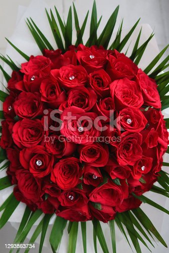 Stock photo of red rose bouquet with small round crystal with green leaves around, romantic floral arrangement for Valentine's Day love theme.