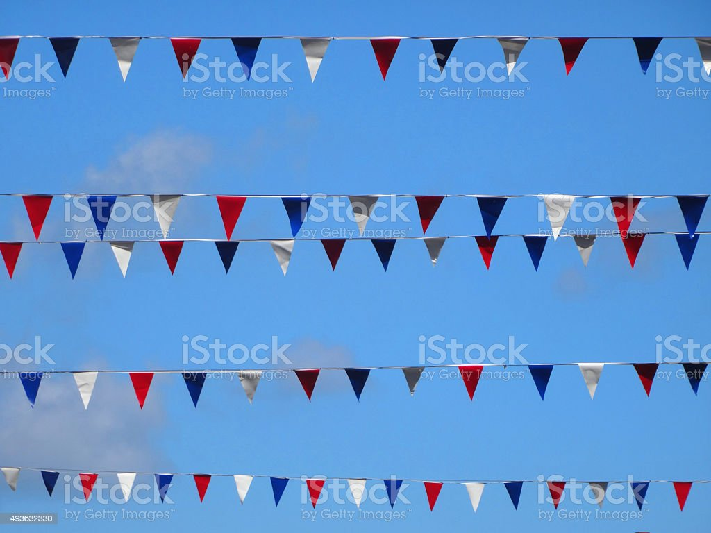 Image of bunting flags in rows against blue sky background stock photo