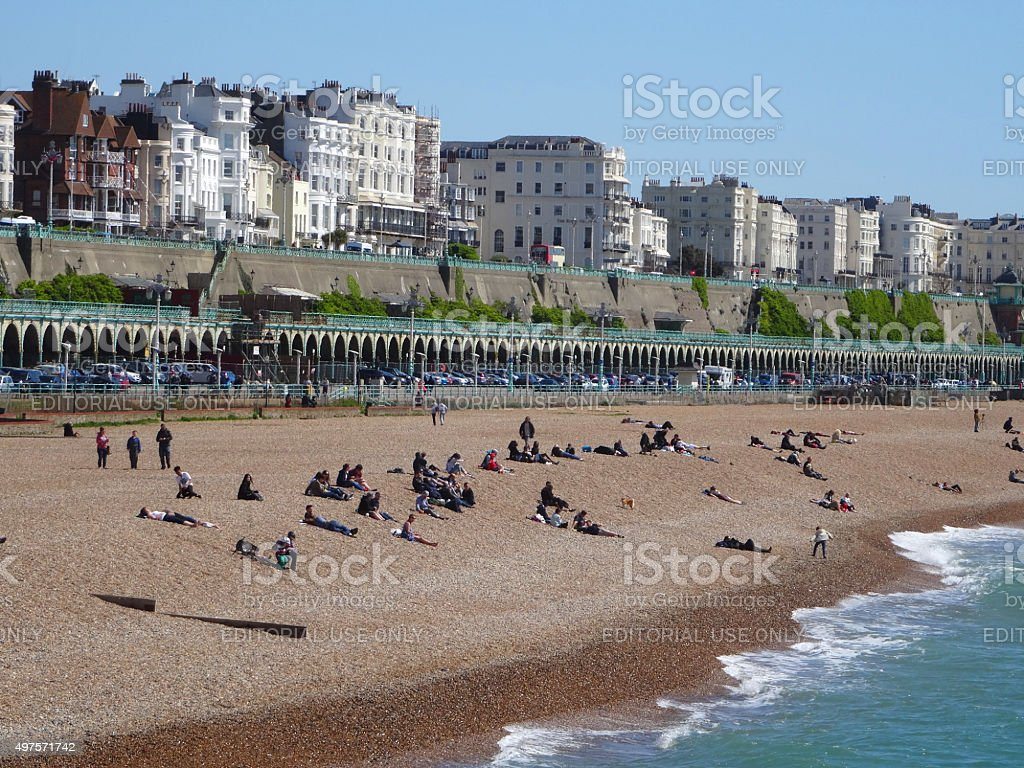Image of busy beach in Brighton with sunbathers / seafront promenade stock photo