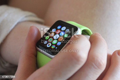 Frome, Somerset, England, UK -  May 13, 2015: Photo showing an Apple Watch Sport model being worn on a girl's left wrist.  This smartwatch has a 38 mm screen in a silver aluminium case with a green, soft plastic sports band. Released on Friday April 24, 2015 the display shows apps available on the watch.