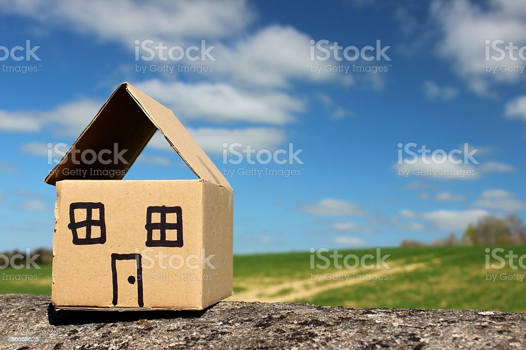 Image of cardboard dolls house, with field and blue sky stock photo