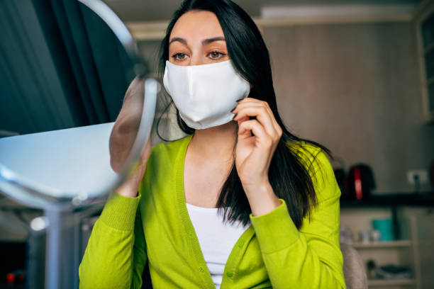 Image of Caucasian woman blogger wearing mask during quarantine, creating new content for her blog on social networks. Female wears mask to protect from virus. Coronavirus, internet, blogging. stock photo