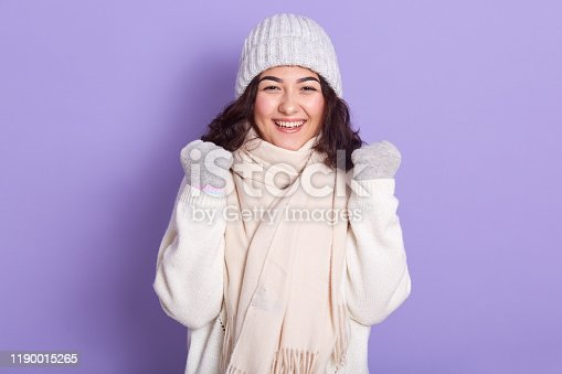 istock Image of cheerful, adorable young model raising her fists, being in high spirits, laughing, being fond of cold weather, wearing warm clothes, looking directly at camera. People and emotions concept. 1190015265