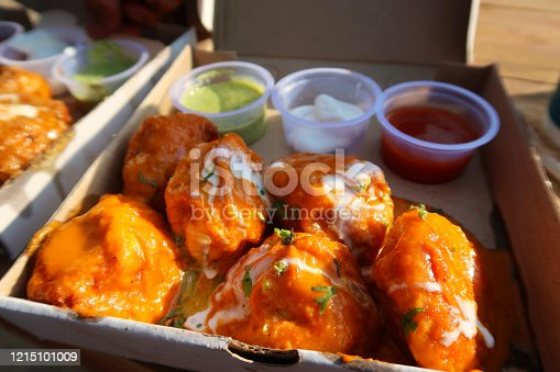 Stock photo showing a cardboard box filled with chicken tikka momos, resembling a traditional chicken tikka masala sauce, complete with spicy tikka sauce and cream / yoghurt curd topping, as well as herbs and spices served with spicy, green and mayonnaise dip. This popular meal is often for sale as street food and is both inexpensive and delicious as an Indian takeaway, being photographed in New Delhi, India.