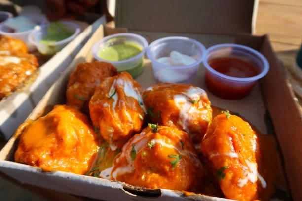 Bild von Huhn Tikka Mütter / hausgemachte Knödel in einem Karton mit fettigen würzigen Tikka-Sauce und Sahne bedeckt / Joghurt, Kräuter und Gewürze, serviert mit würzigen Dips, traditionelle Street Food indische zum Mitnehmen Essen in Neu-Delhi, Indi – Foto