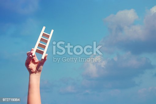 istock image of child hand holding a ladder against the sky. education and success concept. 972719354