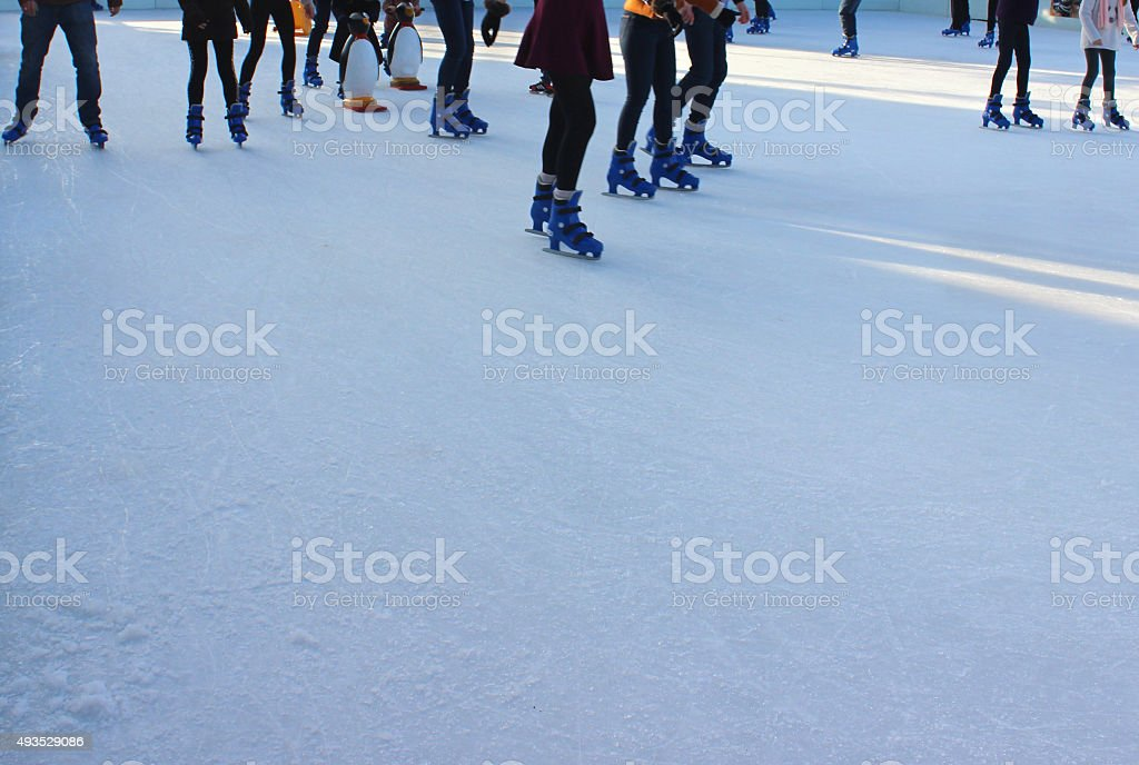 Photo showing some children and their parents who are ice skating...