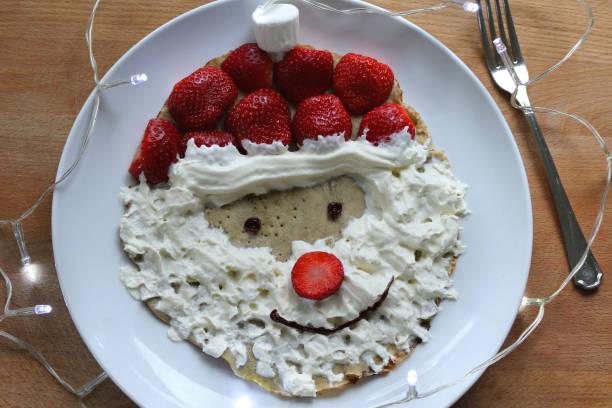 bild von kinder weihnachten weihnachts-weihnachts-pfannkuchen rezept / vater weihnachten pfannkuchen-frühstück mit schlagsahne bart, marshmallow und roten erdbeeren für hut und nase, rosinenaugen, schokolade eismaul, weihnachtsmann essen, frühstück f� - weihnachtsmannhüte aus erdbeeren stock-fotos und bilder