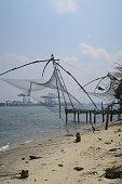 Stock photo of Chinese fishing nets at sunset in Fort Kochi beach in Cochin, Kerala, South India with local Indian fisherman catching tuna fish mackerel from port of Kochi harbour water in Indian Ocean / Arabian Sea, Cheena vala Chinese fishing nets Kochi photo