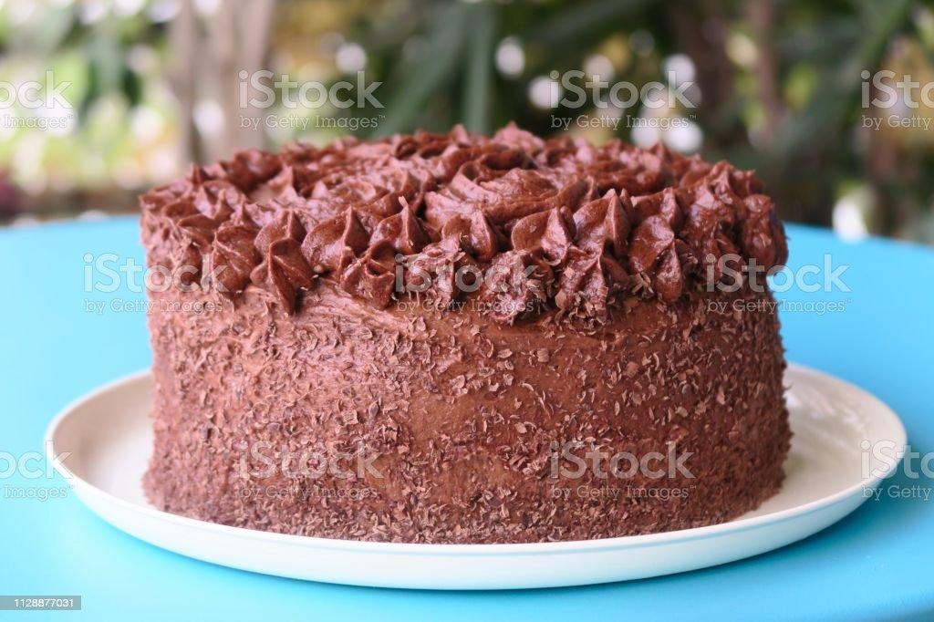 Close-up of chocolate birthday cake covered in chocolate ganache and...
