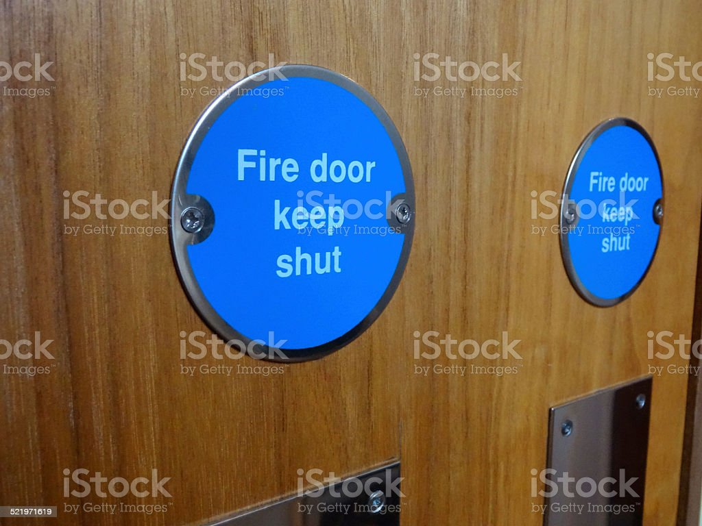 Image of circular blue Fire Door Keep Shut safety sign stock photo