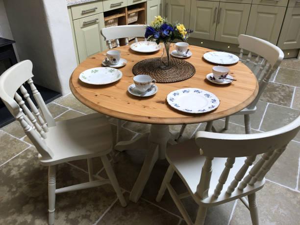 Bild von runden Kiefer Essküchentisch mit vier Stühlen bemalt weiß Set für das Frühstück / Mittagessen mit Tellern, Teetassen und Untertassen, Vase von Blumen und Tischsets, auf Fliesenboden mit Steinfliesen, Küchenschränke / Schränke im Hintergru – Foto