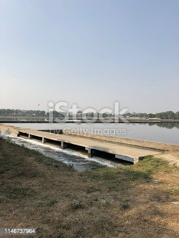 Stock photo of sewage plant in Delhi, India, dirty toilet water waste treated and purified series of filters, mechanical and biological filtration nitrogen cycle, manmade lake appearance.