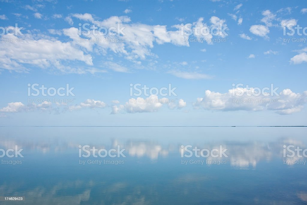 Image of clear blue sky reflecting above the water royalty-free stock photo