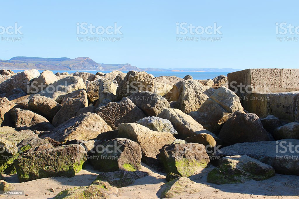 Image of coastal sea defence on sandy beach, natural rock-armour stock photo