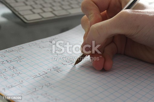 Stock photo of school boy student studying and doing maths homework on paper, with close-up of the student's hand writing fractions notebook, algebra mathematics calculations by computer.
