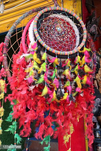 Stock photo showing colourful dream catchers decorated with feathers and beads on Indian market stall.