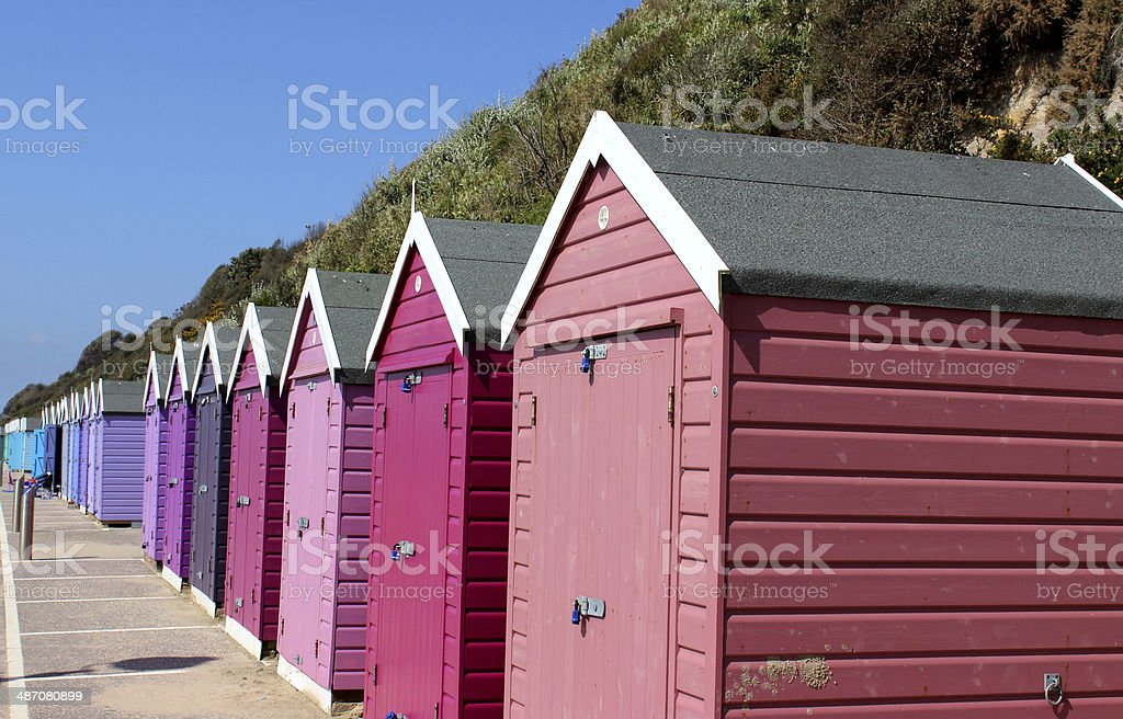 Image of colourful English painted beach huts next to cliff stock photo