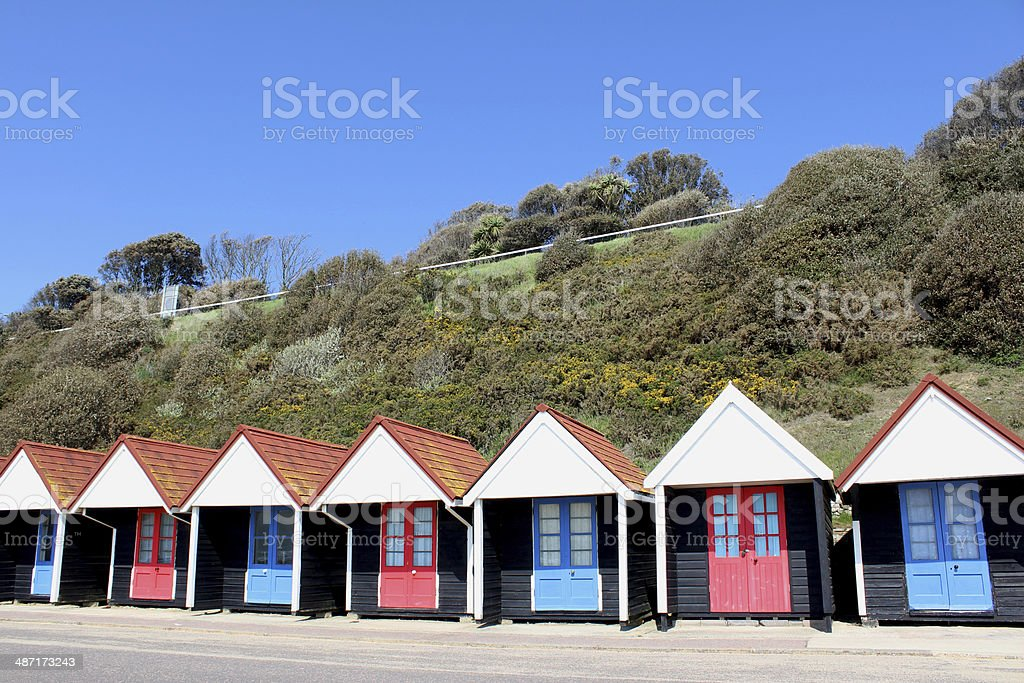 Image of colourful English painted beach huts next to cliff royalty-free stock photo