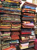 Stock photo of colourful Indian fabric material in piles on shelves, silk scarves, pashminas, bedspreads and shawls at Delhi shopping centre market, Connaught Place, Uttar Pradesh, India