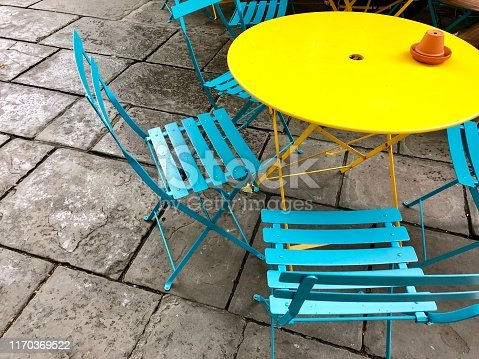 Stock photo showing coloured painted, small circular round metal and wooden garden patio table and chairs in bright colours, yellow and turquoise blue.
