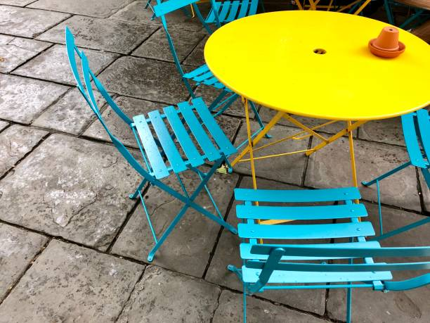 Image of colourfully painted, circular round metal and wooden garden patio tables and chairs in bright colours with rainbow paint, yellow table and turquoise blue chairs stock photo