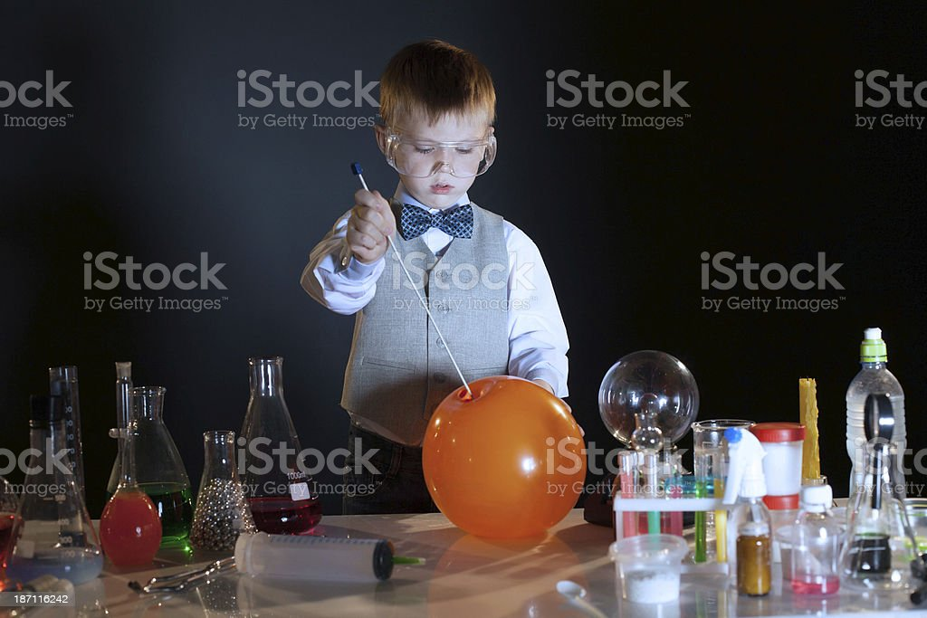 Image of concentrated pupil pierces balloon in lab royalty-free stock photo