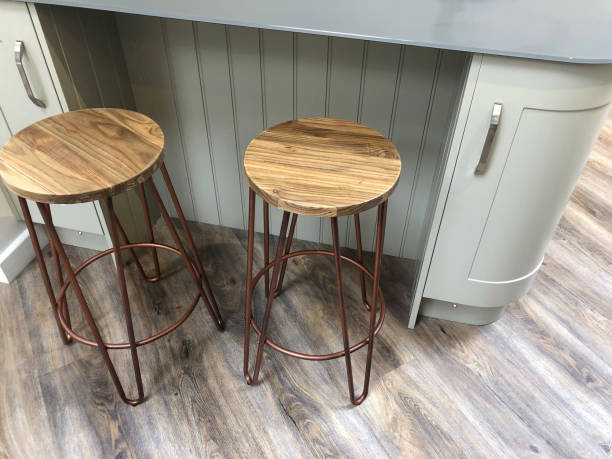 Image of curved kitchen floor cabinets painted duck egg blue, breakfast bar / kitchen island tongue and groove cladding timber, grey composite corian worktop countertop, oak wood stools with copper coloured metal legs on dark oak effect laminate floors stock photo