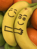 Image of cute banana cuddle in fruit bowl, two ripe yellow bananas cuddling and holding, having sex, making love and spooning with oranges and green apples, fruit couple in love with cartoon faces smiling and sleeping with eyes closed, happy smiley banana