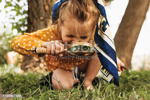 istock Image of cute kid with magnifying glass exploring the nature outdoors. Adorable little girl playing in the forest with magnifying glass. Curious child looking through magnifier on a sunny day in park 1155907435