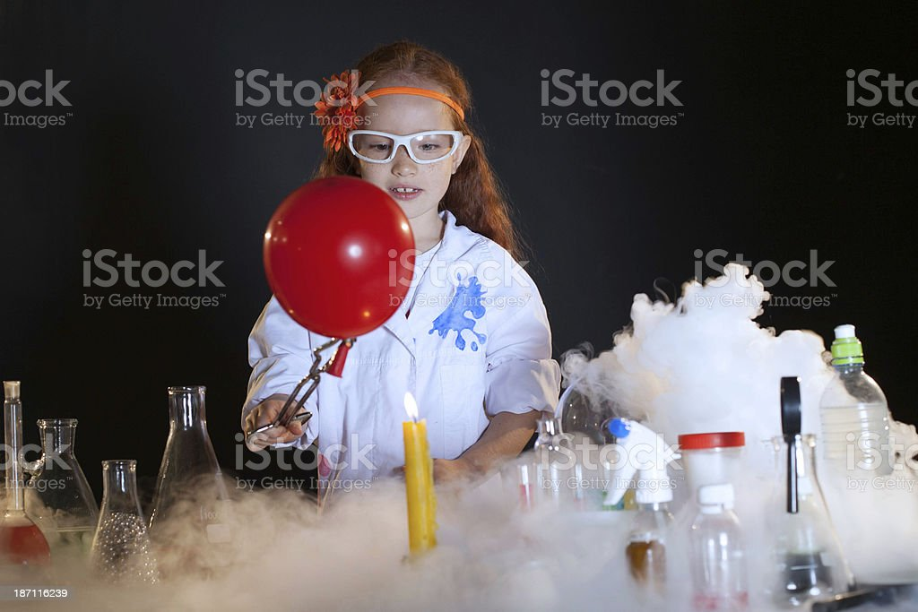 Image of cute little schoolgirl watching reagents royalty-free stock photo
