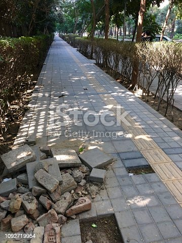 Tripping hazard on public footpath where paving slabs have been removed from a pathway in Delhi, India.