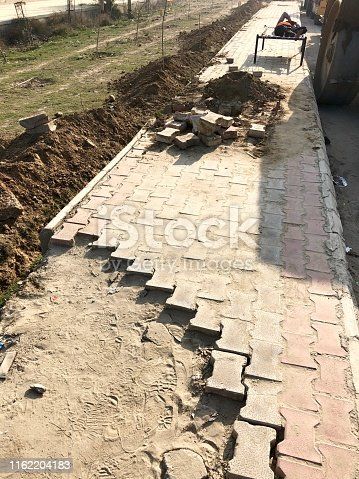 Stock photo of block paving pavement in need of repair, broken dangerous paving photo tripping hazard, builder napping on camp bed on building site construction, Noida, near New Delhi, India.