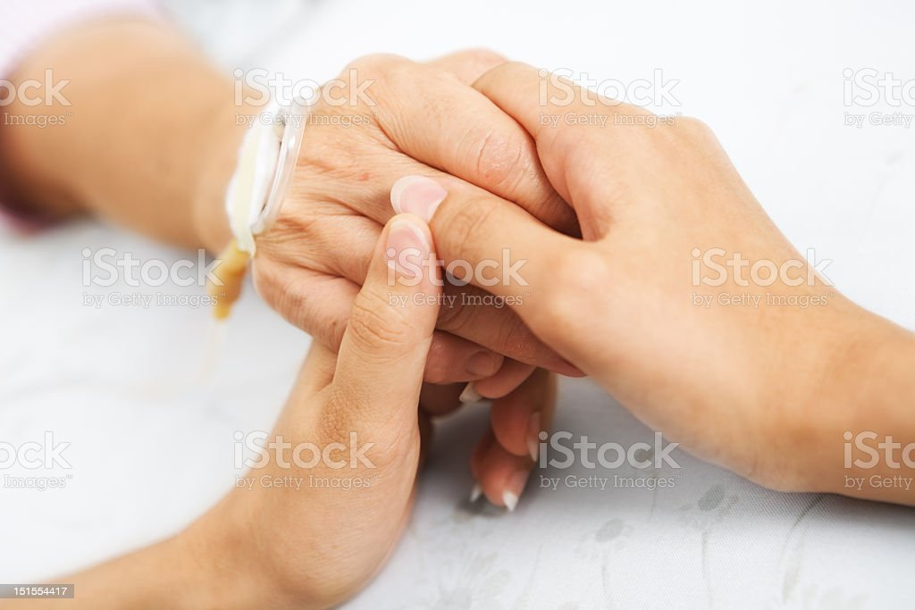 Image of daughter holding mother's hand at hospital bedside stock photo