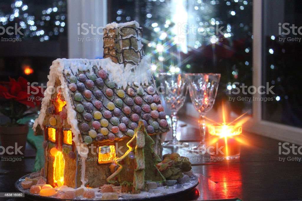 Image of decorated Christmas gingerbread-house at night, fairy-lights and candles stock photo