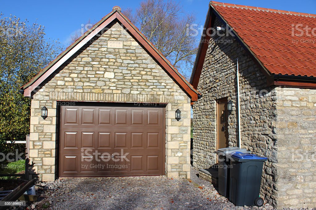 Image of detached garage, up-and-over garage door, bungalow back-door, wheelie-bins stock photo